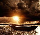 stock photo of life-boat  - Wooden boat in a stormy sea  - JPG