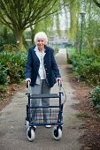 image of street-walker  - Very old lady with blue walker walking outdoor - JPG