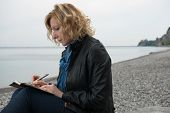 picture of poetry  - Woman writing her thoughts or poetry by the sea - JPG