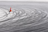 stock photo of skid  - Orange traffic cone and curved car drift skid marks - JPG