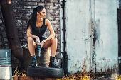stock photo of handgun  - sexy brutal woman sitting in factory ruins and holding handgun