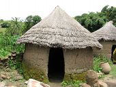 stock photo of mud-hut  - A  mud hut with thatched roof is typical architecture in rural Africa - JPG