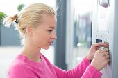 stock photo of automatic teller machine  - Young lady inserting coin in the vending machine - JPG