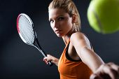 image of indoor games  - Portrait of beautiful woman playing tennis indoor. Isolated on black.
