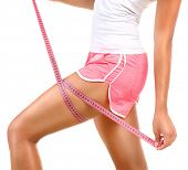 image of measurements  - Fitness sporty woman measuring her hip with a measuring tape - JPG