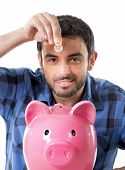 image of spanish money  - young happy man wearing casual shirt holding coin putting it into pink piggy bank in saving money financial and banking concept isolated on white background - JPG