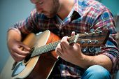 image of fret  - close up of a male musician playing acoustic guitar - JPG