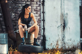 image of raider  - sexy brutal woman sitting in factory ruins and holding handgun