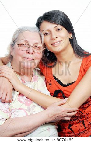 Smiling grandmother and granddaughter embracing