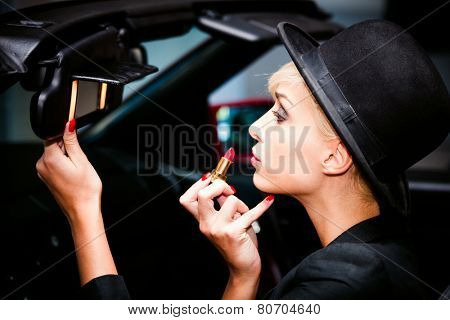 young fashion blonde woman with hat applying red lipstick using car mirror