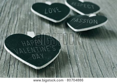 words love, respect and passion, and the sentence happy valentines day written in some heart-shaped chalkboards, on a rustic wooden surface, in black and white