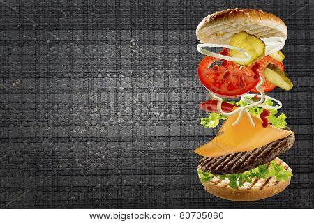 Delicious cheeseburger stacked high with a juicy beef patty, cheese, fresh lettuce, onion and tomato with flying ingredients and copyspace