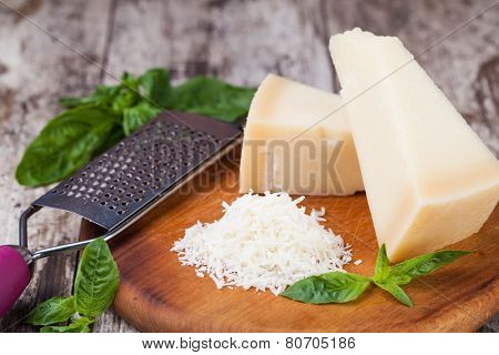 grated parmesan cheese and metal grater on wooden board