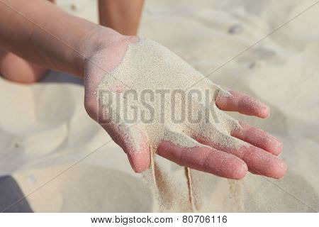 hand pours sand