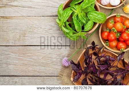 Fresh farmers basil and tomatoes on wood table with copy space