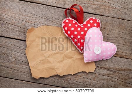 Blank old piece of paper and vintage handmaded valentines day toy hearts over wooden background