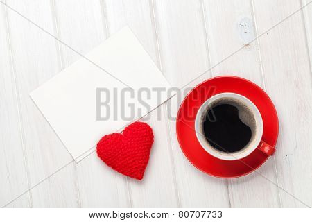Valentines day blank greeting card, coffee cup and heart shaped toy over white wooden table