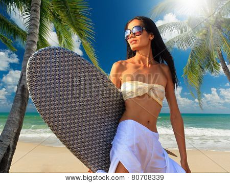 Portrait of a beautiful asian woman holding a surf board