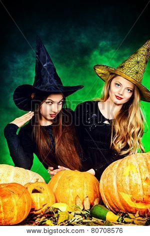Two pretty teen girls in a costumes of witches standing with pumpkins over dark smoky background. Halloween.