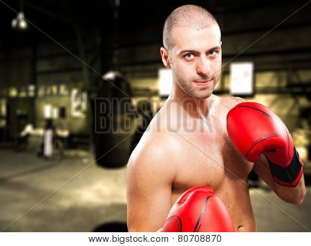 Tough boxer training in an old dark gym