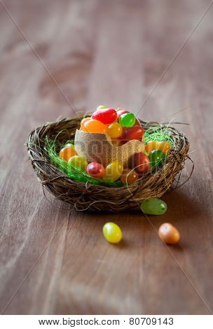 colorful Easter candy eggs in nest on the wooden table. soft focus