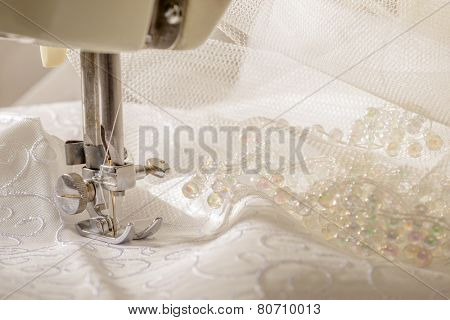 Ivory wedding dress fabric being sewn on vintage machine