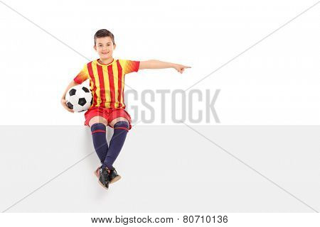 Junior football player pointing with his hand seated on panel isolated on white background