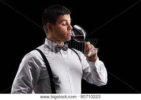 Elegant young guy drinking wine on black background