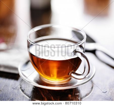 glass of tea with teabag in the background