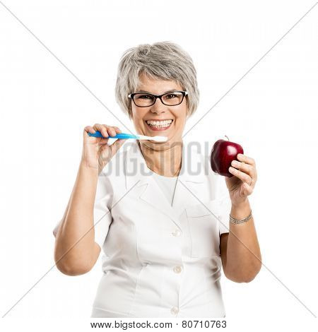 Senior woman with a toothbrush and a apple