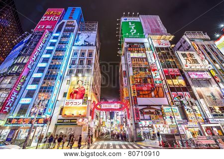 TOKYO, JAPAN - MARCH 14, 2014: Pedestrians walk below signs densely lining an alleyway in Kabuki-cho. The area is a renown nightlife and red-light district.