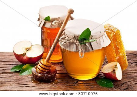 Glass cans full of honey, apples, honeycombs old wooden table. File contains clipping paths.