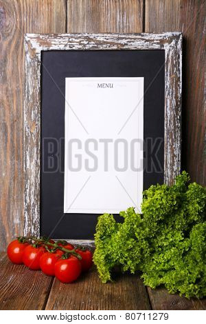 Menu board on rustic wooden planks background with cherry tomatoes and lettuce on rustic wooden planks background
