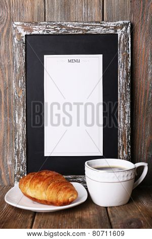 Menu board with cup of coffee and croissant on rustic wooden planks background