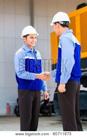 Asian engineer having agreement handshake at construction machinery of construction site or mining company