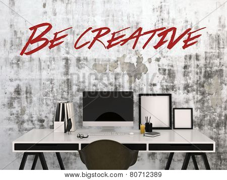 3D Rendering of Be Creative concept with the text in red on an abstract grey wall above a stylish black and white desk with desktop computer, photo frames , and pens in a business or home office