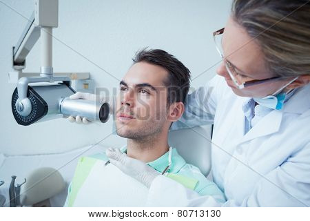 Serious young man undergoing dental checkup in the dentists chair