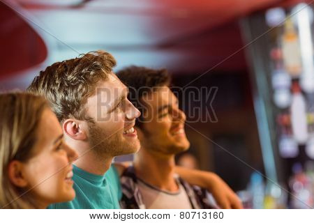Smiling brown hair standing with arm around his friends in a bar