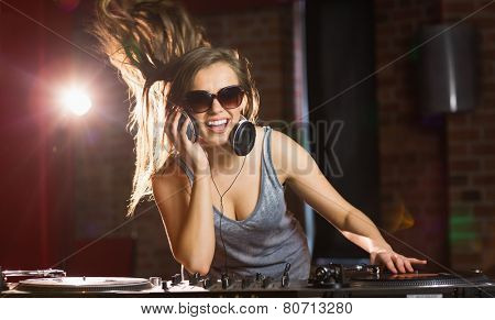 Pretty dj smiling and dancing at the nightclub