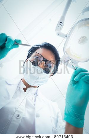 Low angle view of female dentist in surgical mask holding dental tools