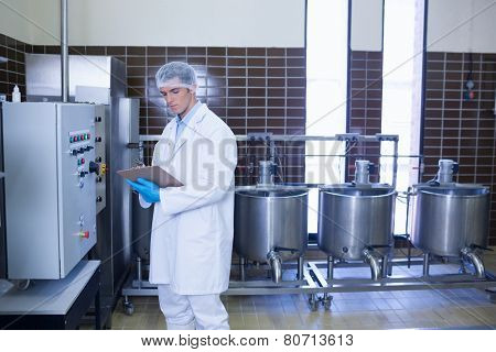 Focused biologist with safety gloves holding clipboard in the factory