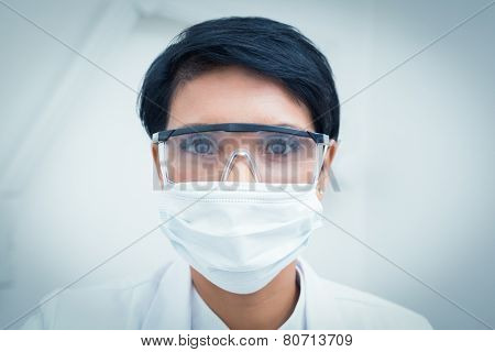Portrait of female dentist wearing surgical mask and safety glasses