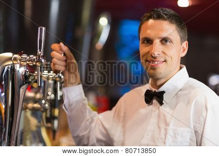 Handsome barman smiling at camera in a bar