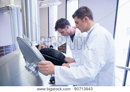 Two scientists looking into the container in the factory