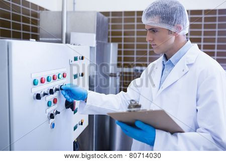 Focused biologist using the machine in the factory