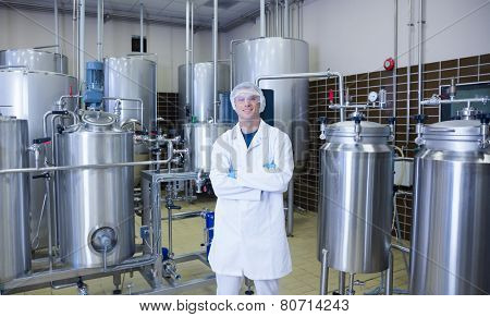 Scientist with arms crossed standing in front of container in the factory