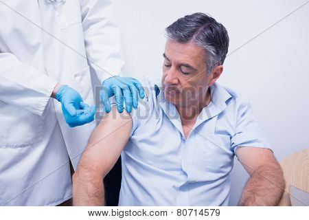 Doctor giving injection to his patient at the hospital