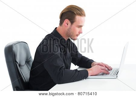 Concentrated businessman using laptop at desk on white background