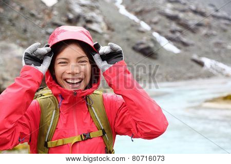 Laughing happy woman hiking with backpack in rain on trek living healthy active lifestyle. Smiling cheerful girl walking on hike in beautiful mountain nature landscape raining, Swiss alps, Switzerland