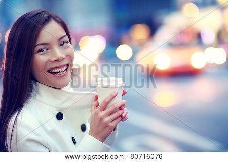 Professional young urban casual business woman happy in New York City Manhattan drinking coffee walking in street wearing coat downtown with yellow taxi cabs in background.